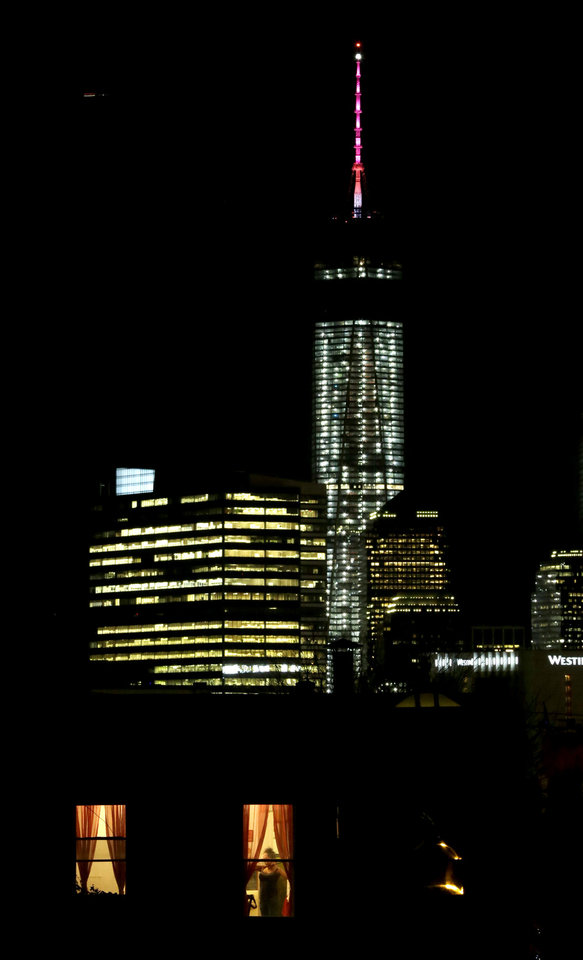 Photo - A woman talking on a phone is seen through a window of a home in The Heights neighborhood of Jersey City, N.J., with One World Trade Center as a backdrop, Friday, Nov. 8, 2013. The Port Authority of New York and New Jersey, who tested the lights on Friday, said the beacon is packed with nearly 300 modules and their glow can be seen for up to 50 miles. The beacon and spire together stand 408 feet tall and bring the building, formerly called the Freedom Tower, to its symbolic height of 1,776 feet. The Durst Organization operates the spire, which will serve broadcasters. (AP Photo/Julio Cortez)