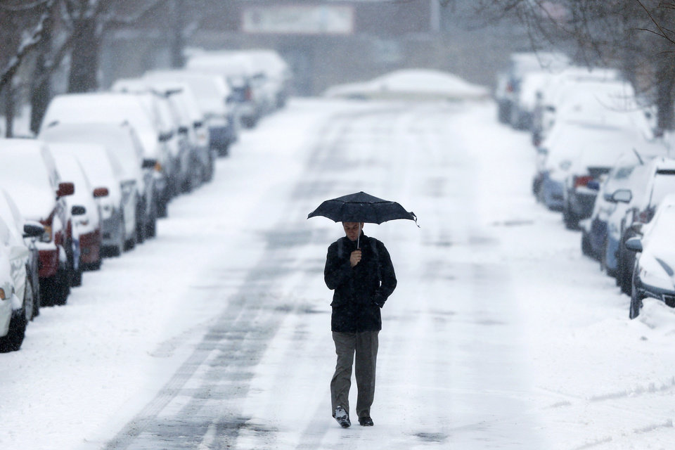 Photo - A morning commuter walks to a train station during a winter snowstorm Monday, March 3, 2014, in Philadelphia. Spring is in sight, but winter kept its icy hold on much of the country Monday, with up to a foot of snow and plummeting temperatures expected across the Mid-Atlantic states and up the East Coast. (AP Photo/Matt Rourke)