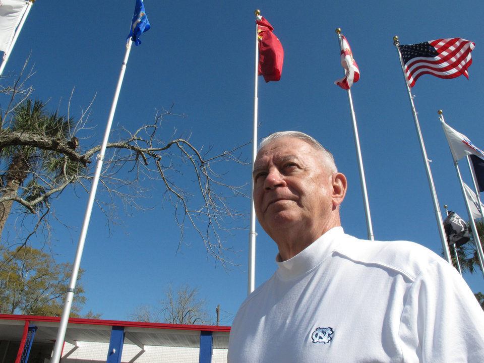 Photo - Len Loving, chief executive of the Allied Veterans Center, stands beneath the flagpoles outside the shelter for homeless veterans in Jacksonville, Fla., on Thursday, March 14, 2013. Loving says he may have to close the center by the end of June for lack of funding. The shelter gets almost all of its money from Allied Veterans of the World, a Florida organization that's had its top officers arrested and assets seized as part of an illegal gambling investigation. (AP Photo/Russ Bynum)