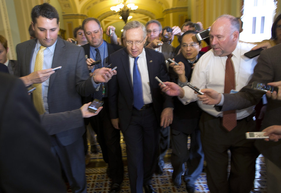 Photo - Senate Majority Leader Sen. Harry Reid, D-Nev., is surrounded by reporters after leaving the office of Senate Minority Leader Sen. Mitch McConnell, R-Ken., on Capitol Hill on Monday, Oct. 14, 2013 in Washington. Reid reported progress Monday towards a deal to avoid a threatened default and end a two-week partial government shutdown as President Barack Obama called congressional leaders to the White House to press for an end to the impasse.