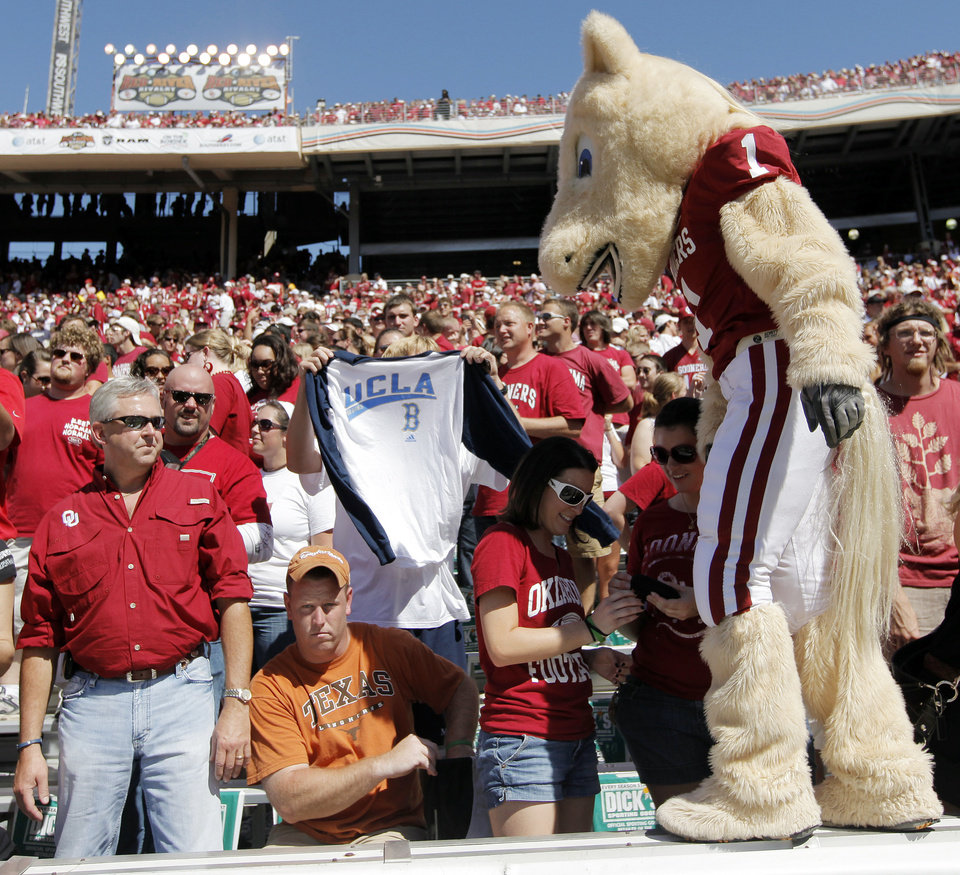 OU mascot Boomer looks at a Texas fan sitting among the Sooner fans before the Red River Rivalry college football game between the University of Oklahoma Sooners (OU) and the University of Texas Longhorns (UT) at the Cotton Bowl on Saturday, Oct. 2, 2010, in Dallas, Texas. Photo by Nate Billings, The Oklahoman