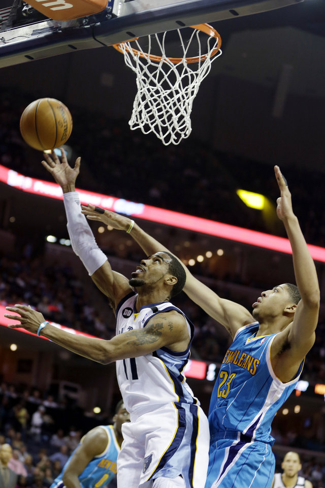Photo - Memphis Grizzlies' Mike Conley (11) goes to the basket in front of New Orleans Hornets' Anthony Davis (23) during first half of an NBA basketball game in Memphis, Tenn., Saturday, March 9, 2013. (AP Photo/Danny Johnston)