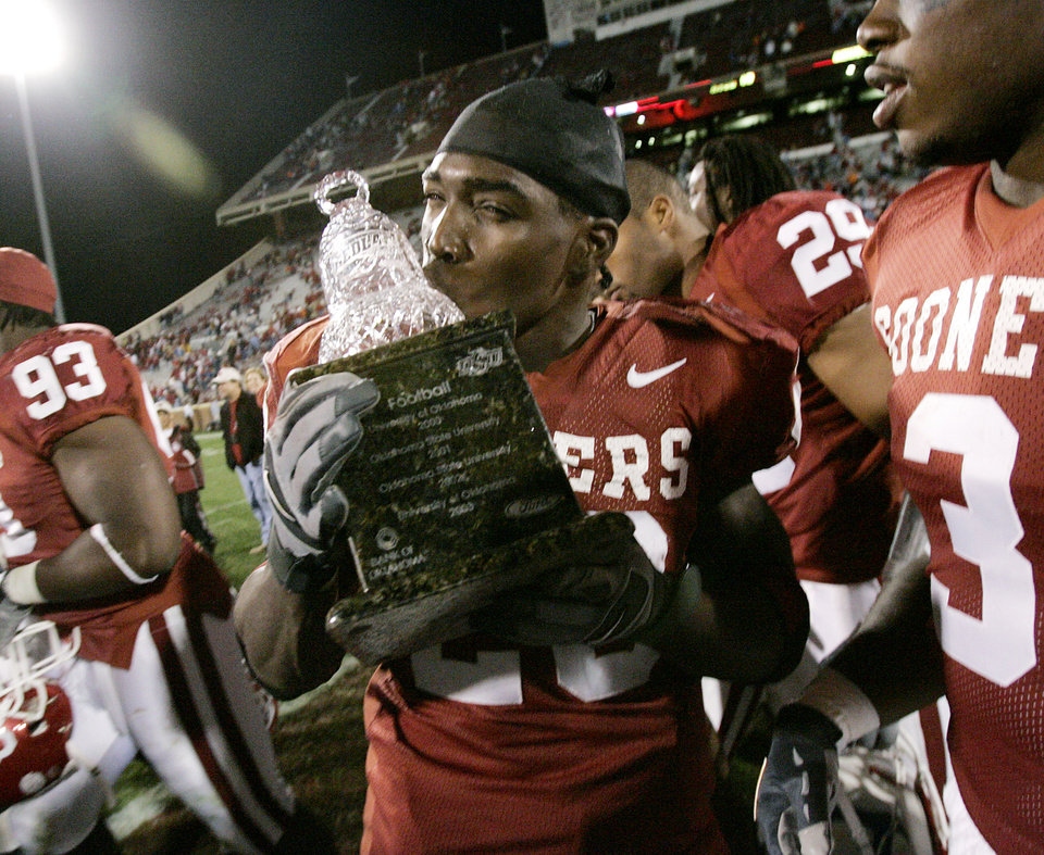 Kejuan Jones of OU kisses the Bedlam trophy after the University of Oklahoma Sooners college football game against Oklahoma State University, at Gaylord Family-Oklahoma Memorial Stadium, Saturday, November 26, 2005, in Norman, Oklahoma.  This is the 100th Bedlam football game. By Bryan Terry/The Oklahoman