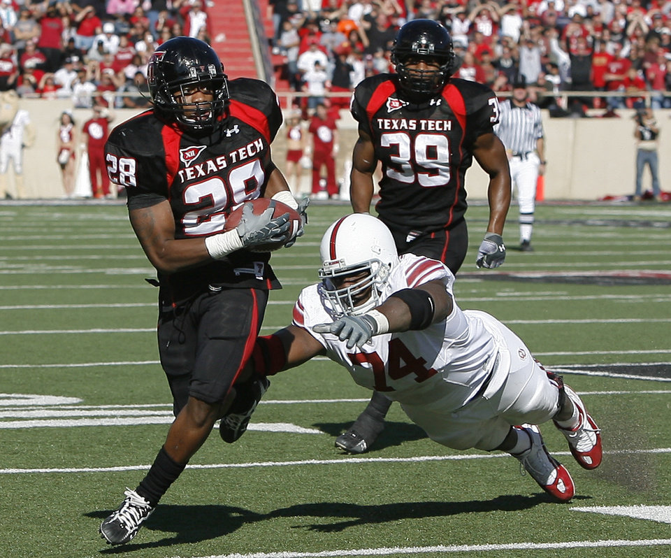 Photo - Texas Tech's LaRon Moore runs past OU's Brian Simmons after an interception during the college football game between the University of Oklahoma Sooners (OU) and Texas Tech University Red Raiders (TTU ) at Jones AT&T Stadium in Lubbock, Texas, Saturday, Nov. 21, 2009. Photo by Bryan Terry, The Oklahoman