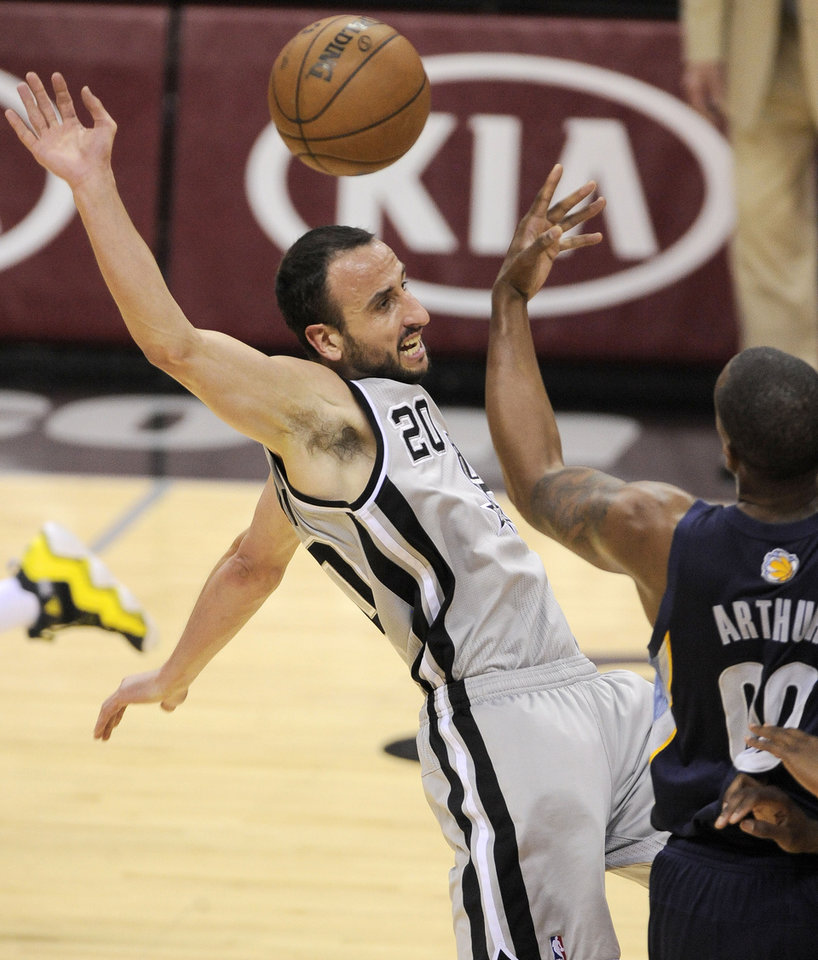 Photo - San Antonio Spurs' Manu Ginobili, left, of Argentina, falls after tangling with Memphis Grizzlies' Darrell Arthur during the first half of Game 1 of the Western Conference final NBA basketball playoff series Sunday, May 19, 2013, in San Antonio. (AP Photo/Darren Abate)