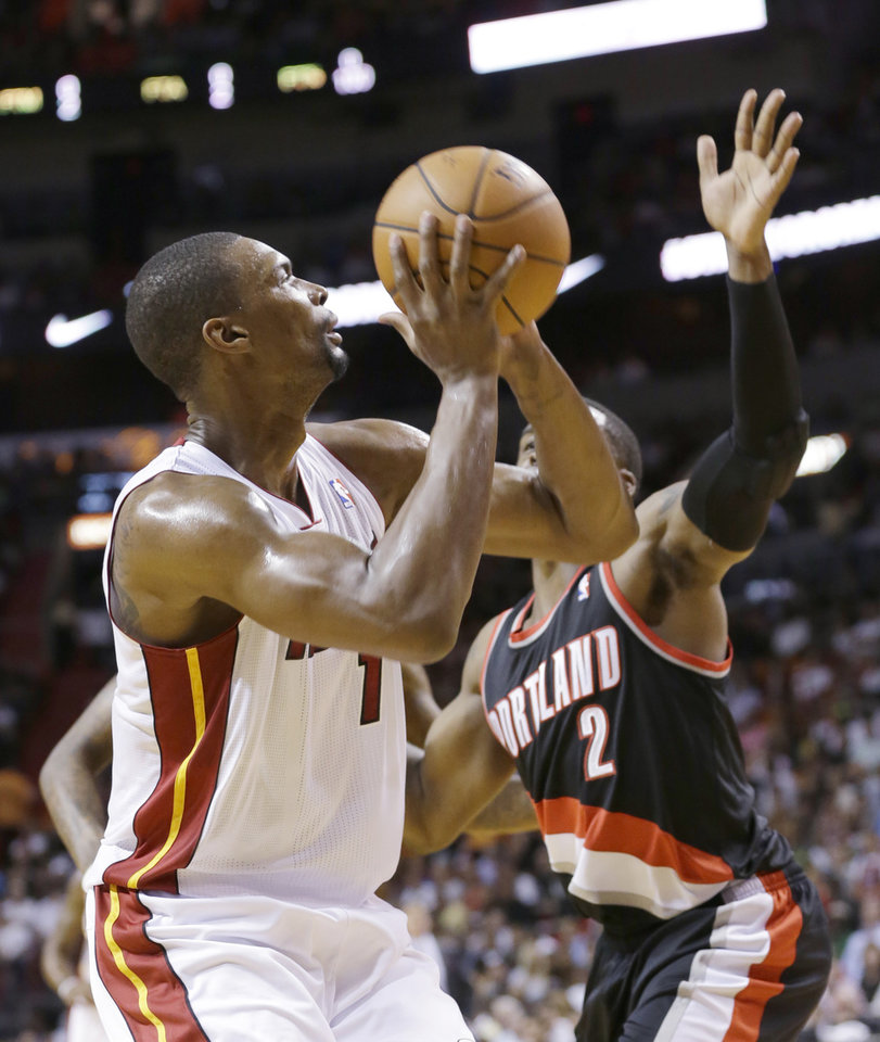 Photo - Miami Heat center Chris Bosh (1) goes up for a shot against Portland Trail Blazers guard Wesley Matthews (2) during the first half of an NBA basketball game, Monday, March 24, 2014 in Miami. Bosh finished with 15 points as the Heat defeated the Trail Blazers 93-91. (AP Photo/Wilfredo Lee)
