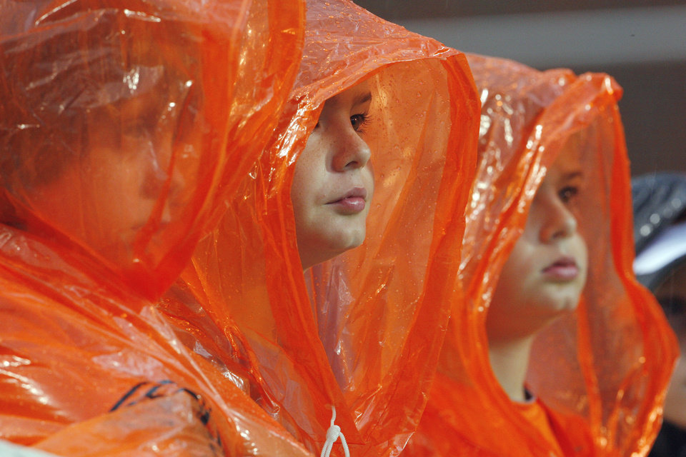 Photo - Oklahoma State fans wear rain gear during the second half of a college football game where the Oklahoma State University Cowboys (OSU) defeated the University of Kansas Jayhawks (KU) 70-28 at Boone Pickens Stadium in Stillwater, Okla., Saturday, Oct. 8, 2011 Photo by Steve Sisney, The Oklahoman