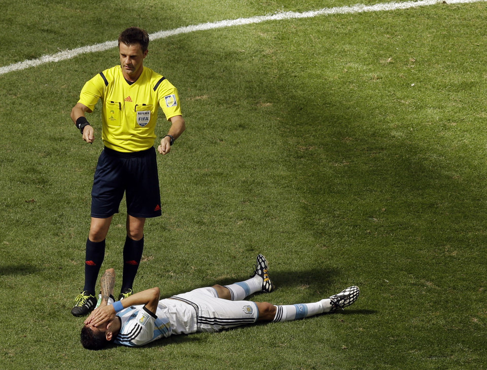 Photo - Referee Nicola Rizzoli from Italy request a stretcher as Argentina's Angel di Maria lies on the ground during the World Cup quarterfinal soccer match between Argentina and Belgium at the Estadio Nacional in Brasilia, Brazil, Saturday, July 5, 2014. (AP Photo/Thanassis Stavrakis)