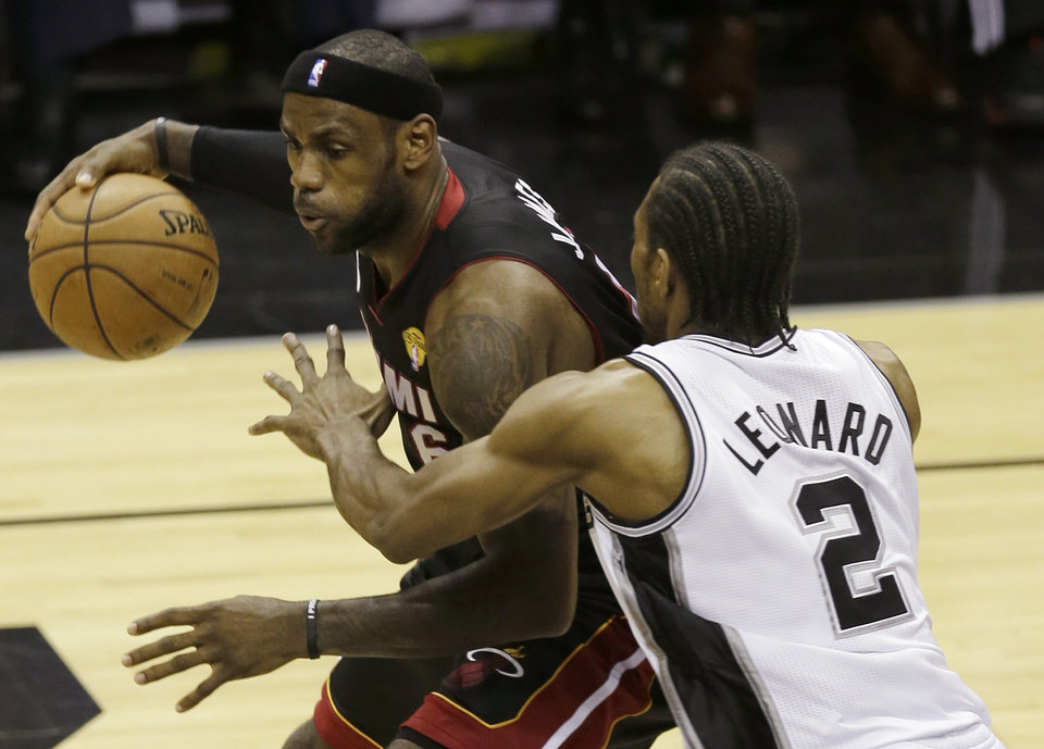 Photo - Miami Heat's LeBron James (6) is defended by San Antonio Spurs' Kawhi Leonard (2) during the first half at Game 4 of the NBA Finals basketball series, Thursday, June 13, 2013, in San Antonio. (AP Photo/David J. Phillip)