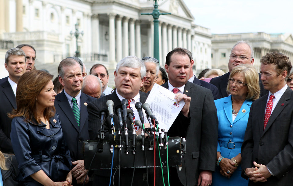 Photo - Tom Zawistowki, founder of the nonprofit Ohio Liberty Coalition, center, speaks during a news conference on Capitol Hill in Washington, Thursday, May 16, 2013, with Tea Party leaders to discuss the IRS targeting Tea Party groups. Rep. Michele Bachmann, R-Minn., chair of the Tea Party Caucus, is at left, Sen. Rand Paul, R-Ky. is at right.  (AP Photo/Molly Riley)