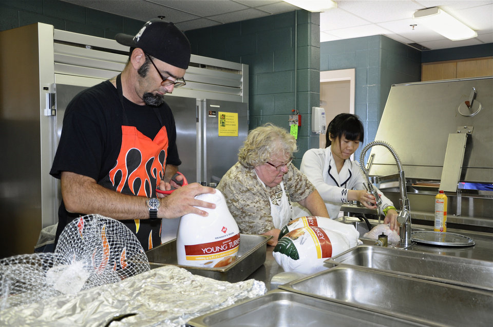 Meihua Guo, Carolyn Sullivan and Frank Paradise Jr. help prepare food for the Edmond Community Thanksgiving Dinner. Photo by M. Tim Blake, for The Oklahoman