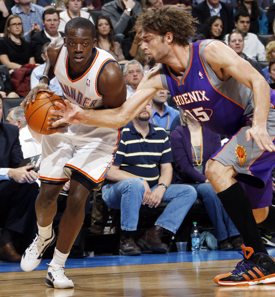 Photo - Oklahoma City's Reggie Jackson (15) keeps the ball away from Phoenix's Robin Lopez (15) in the fourth quarter during the NBA basketball game between the Oklahoma City Thunder and Phoenix Suns at Chesapeake Energy Arena in Oklahoma City, Saturday, Dec. 31, 2011. Oklahoma City won, 107-97. Photo by Nate Billings, The Oklahoman