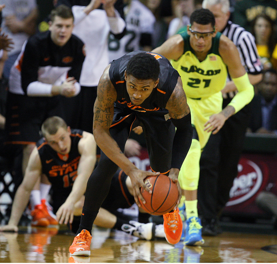 Photo - Oklahoma State forward Le'Bryan Nash (2) picks up a loose ball while heading up court past Baylor center Isaiah Austin (21), right, in the first half of an NCAA college basketball game, Monday, Feb. 17, 2014, in Waco, Texas. (AP Photo/Waco Tribune Herald, Rod Aydelotte)