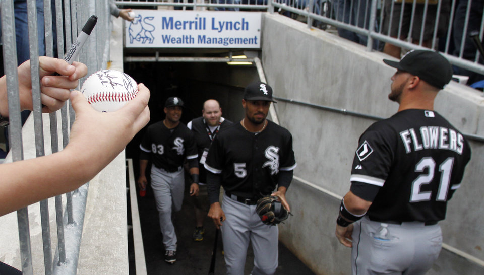 Photo - A young fan holds out a baseball for an autograph as players from the Chicago White Sox take the field before a spring exhibition baseball game against the Birmingham Barons on Friday, March 28, 2014, in Birmingham, Ala. (AP Photo/Butch Dill)