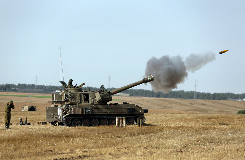 Photo - Israeli soldiers on a mobile artillery unit fire a shell towards Gaza at a position on the Israel-Gaza border, Saturday, July 12, 2014. Israeli airstrikes overnight targeting Hamas in Gaza hit a mosque its military says concealed the militant group's weapons, in an offensive that showed no signs of slowing down. Israel launched its campaign five days ago to stop relentless rocket fire on its citizens. While there have been no fatalities in Israel, Palestinian officials said overnight attacks raised the death toll there to over 120, with more than 920 wounded. (AP Photo/Lefteris Pitarakis)