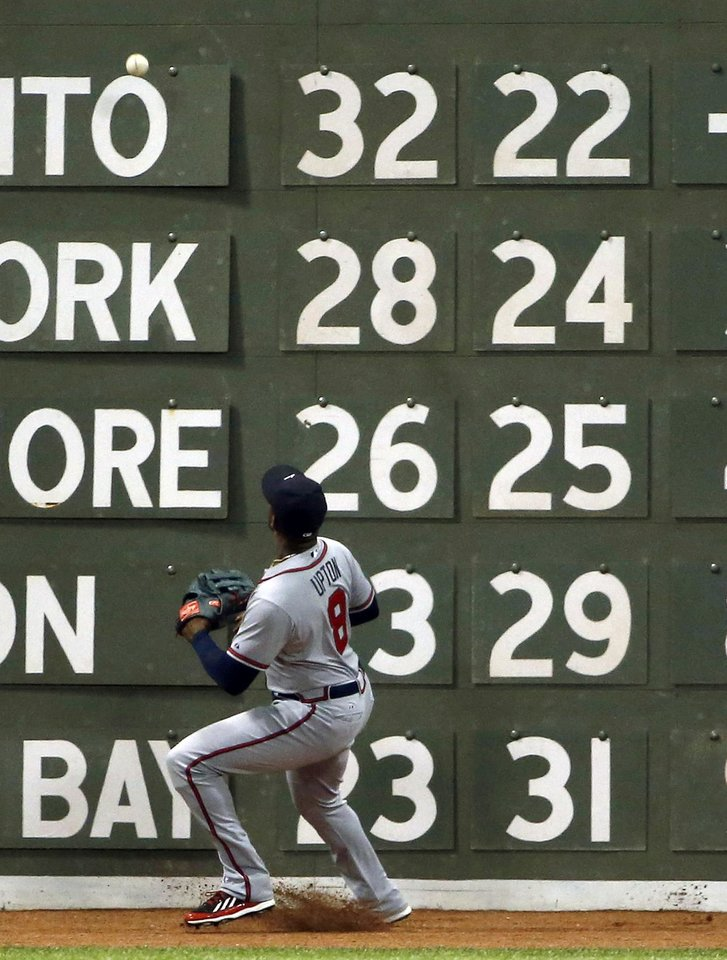 Photo - Atlanta Braves left fielder Justin Upton watches an RBI double by Boston Red Sox's Brock Holt hit off the wall during the fifth inning of a baseball game at Fenway Park, Thursday, May 29, 2014, in Boston. (AP Photo/Winslow Townson)