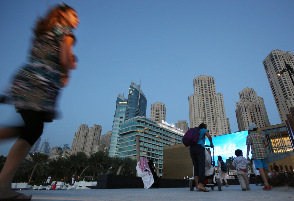 Photo - In this Monday, April 21, 2014 photo, people prepare to watch a movie at an outdoor cinema at the beach in Dubai, United Arab Emirates. Most of the luxury towers along the beach have been built only in the past decade. Some are homes to foreign professionals working in the Gulf commercial hub, others vacation properties or a place to park some cash for wealthy businesspeople from Russia, Asia and nearby Saudi Arabia. (AP Photo/Kamran Jebreili)