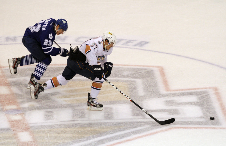 OKC\'s Anton Lander (37) and Toronto\'s Matt Frattin (23) skate during a game between the Oklahoma City Barons and the Toronto Marlies at the Cox Convention Center in Oklahoma City, Friday, May 18, 2012. Photo by Garett Fisbeck, For The Oklahoman