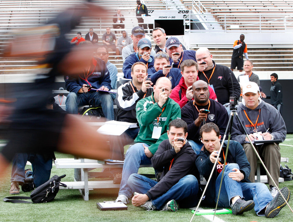 NFL scouts check their stop watches during the 40 yard dash at Boone Pickens Stadium in Stillwater, Oklahoma March 10 , 2010. Photo by Steve Gooch, The Oklahoman