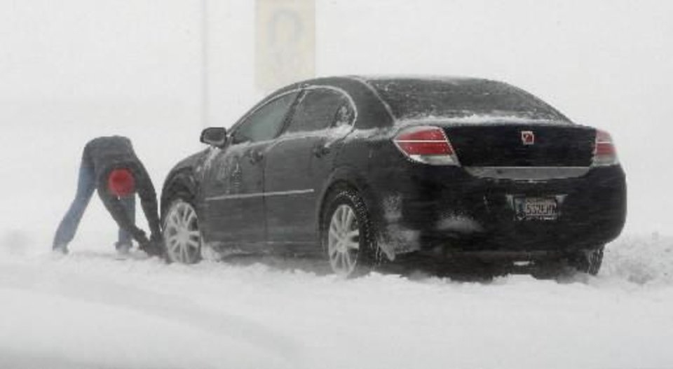 Photo - A motorist tries to free their car stuck in a snow drift in the southbound lanes of SH 81 just south of I-40 in El Reno Thursday, Dec. 24, 2009. Photo by  Paul B.  Southerland