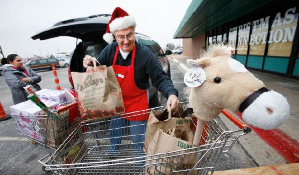 Photo - Volunteer Frank Friedhoff moves toys and clothes into the back of Leticia Walker's van at the Christmas Connection in southwest Oklahoma City. PHOTO BY JIM BECKEL,  THE OKLAHOMAN
