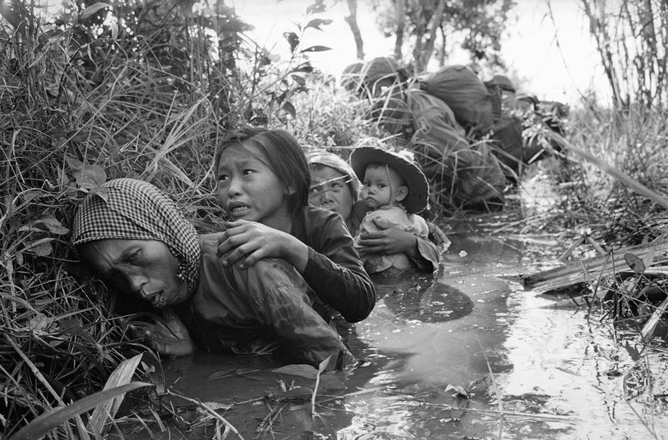 Photo -   FILE - In this Jan. 1, 1966 file photo taken by Associated Press photographer Horst Faas, women and children crouch in a muddy canal as they take cover from intense Viet Cong fire at Bao Trai, about 20 miles west of Saigon, Vietnam. Faas, a prize-winning combat photographer who carved out new standards for covering war with a camera and became one of the world's legendary photojournalists in nearly half a century with The Associated Press, died Thursday May 10, 2012. He was 79. (AP Photo/Horst Faas)