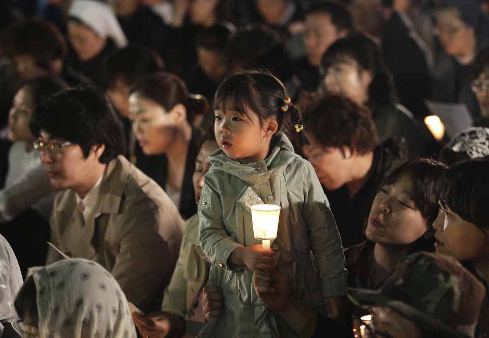 Photo - A girl holds a candle during a service to pay tribute to the victims of the sunken ferry Sewol in Seoul, South Korea, Wednesday, April 30, 2014. Two weeks after the ferry sank off South Korea's southern cost, divers have recovered over 200 bodies from the wreckage, but they fought strong currents and floating debris inside the ship Wednesday as they searched for 90 passengers still missing.(AP Photo/Ahn Young-joon)