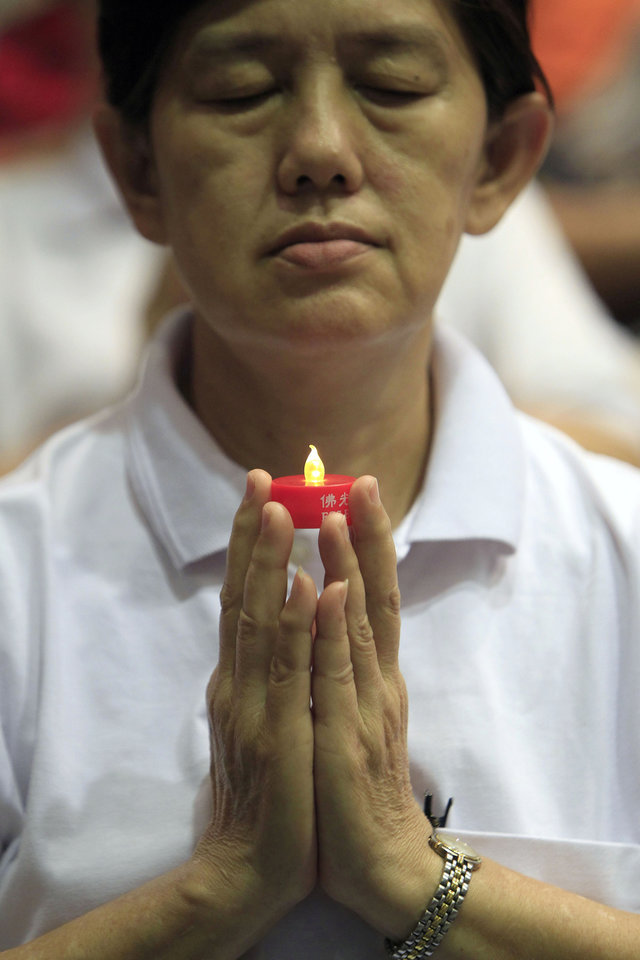 Photo - A woman holding a LED candle offers prayers for passengers aboard the missing Malaysia Airlines Flight MH370, in Kuala Lumpur, Malaysia, Sunday, April 6, 2014. The head of the multinational search for the missing Malaysia airlines jet said that electronic pulses reportedly picked up by a Chinese ship are an encouraging sign but stresses they are not yet verified. (AP Photo/Lai Seng Sin)