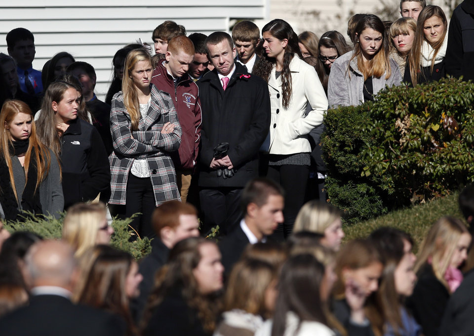 Photo - Students and other mourners watch as the funeral procession of slain Danvers High School teacher Colleen Ritzer begins to move from St. Augustine Church in Andover, Mass., Monday Oct. 28, 2013 after her funeral service. (AP Photo/Elise Amendola)