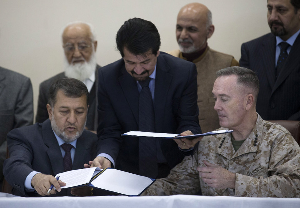 Photo - Afghan Defense Minister General Bismillah Khan, left, signs the papers to hand over the Parwan Detention Facility to Afghan authorities with top U.S commander in Afghanistan General Joseph Dunford in Bagram, outside Kabul, Afghanistan, Monday, March 25, 2013. The handover of Parwan Detention Facility ends a bitter chapter in American relations with Afghanistan's mercurial president, Hamid Karzai, who demanded control of the prison as a matter of national sovereignty. (AP Photo/Anja Niedringhaus)