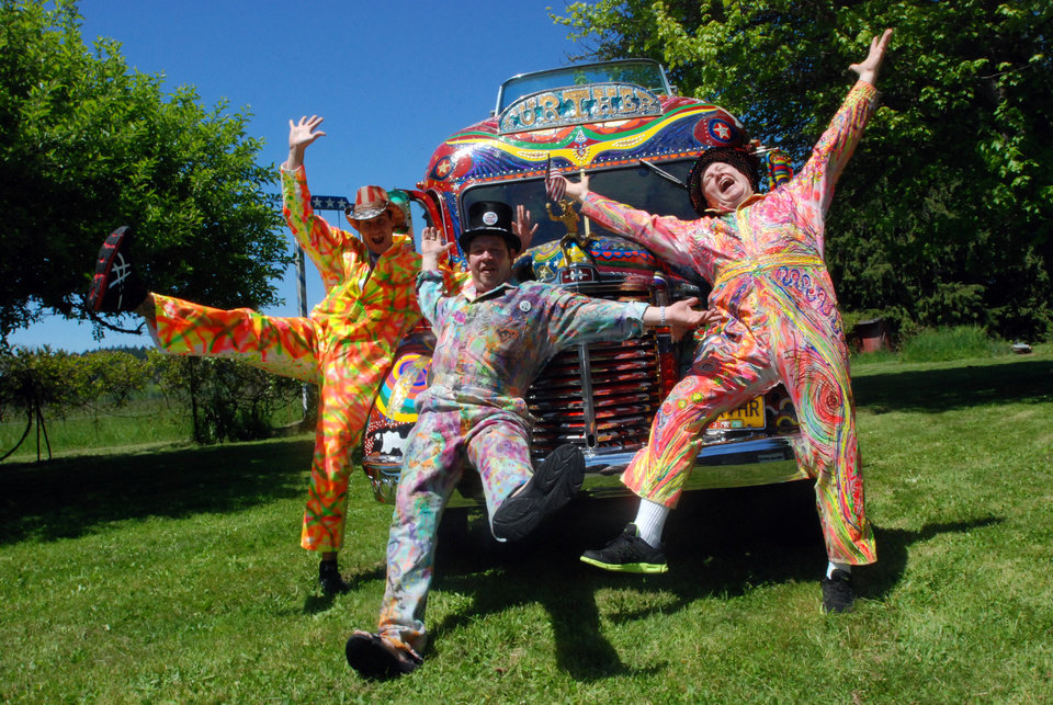 Photo - In a May 14, 2014 photo, Zane Kesey, right, Derek Stevens, center, and Alex Sanford pose with the reincarnated version of author Ken Kesey's psychedelic bus, Further, on the Kesey family farm in Pleasant Hill, Ore. Zane Kesey is on Kickstarter to raise money for a trip across America commemorating his father's LSD-fueled 1964 bus trip that became a touchstone of the psychedelic 1960s. (AP Photo/Jeff Barnard)