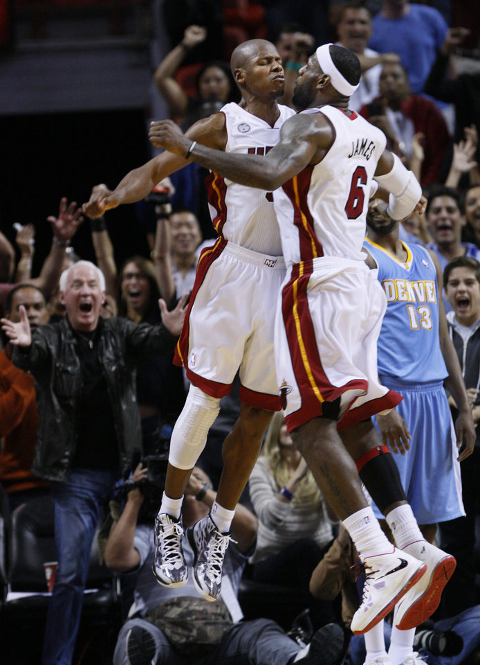 Miami Heat guard Ray Allen, left, celebrates with forward LeBron James (6) after Allen scored in the final seconds of the second half of an NBA basketball game against the Denver Nuggets, Saturday, Nov. 3, 2012 in Miami. Allen had a four-point play with 6.7 seconds left that put Miami ahead for good, Chris Bosh scored 40 points and the Heat held off the Denver Nuggets 119-116. (AP Photo/Wilfredo Lee)