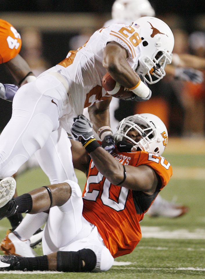 Photo - OSU's Andre Sexton (20) brings down Fozzy Whittaker (28) of Texas during the college football game between the Oklahoma State University Cowboys (OSU) and the University of Texas Longhorns (UT) at Boone Pickens Stadium in Stillwater, Okla., Saturday, Oct. 31, 2009. Photo by Nate Billings, The Oklahoman