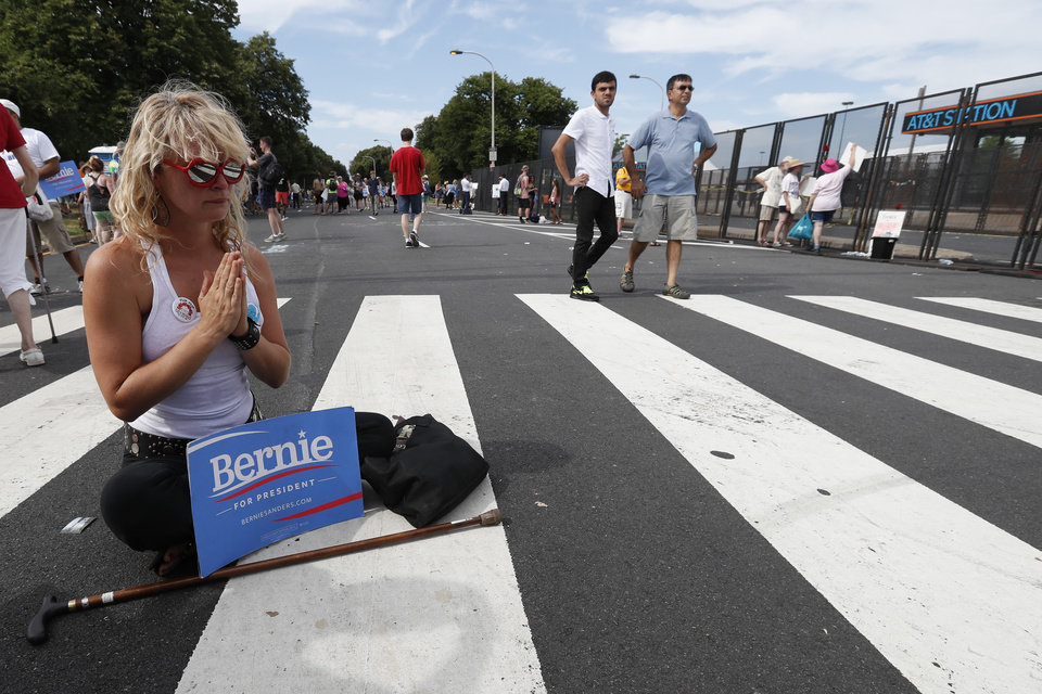 Photo - Angel Settell, a supporter of Sen. Bernie Sanders, I-Vt., prays in the middle of the street at Franklin Delano Roosevelt Park in Philadelphia, Tuesday, July 26, 2016, during the second day of the Democratic National Convention. (AP Photo/Alex Brandon)