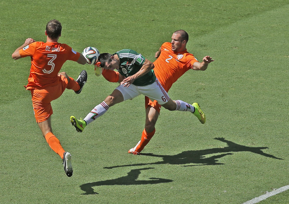 Photo - Mexico's Hector Herrera, center, challenges for the ball with Netherlands' Stefan de Vrij, left, and Ron Vlaar during the World Cup round of 16 soccer match between the Netherlands and Mexico at the Arena Castelao in Fortaleza, Brazil, Sunday, June 29, 2014. (AP Photo/Themba Hadebe)