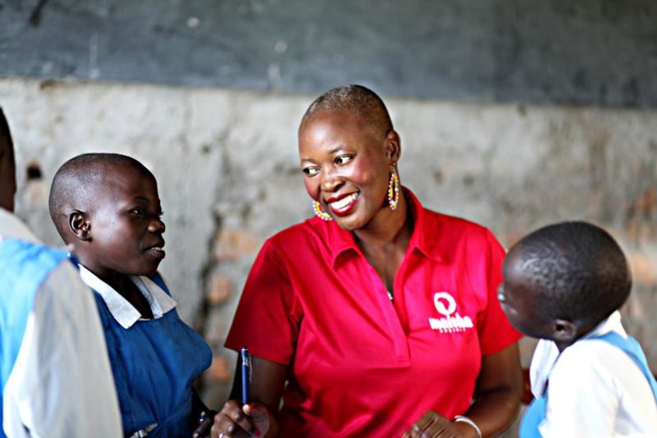 Photo - Maisha Project Executive Director Beatrice Williamson shares a momemt with sponsored children schoolchildren in Kenya. [PHOTO PROVIDED]