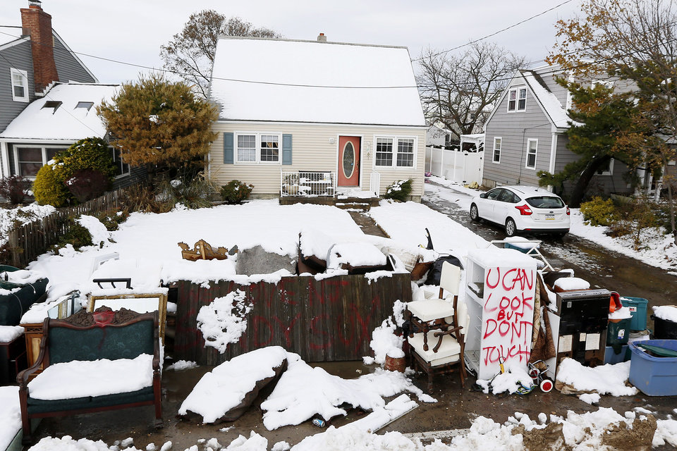 Photo - Messages are written on snow covered debris from Superstorm Sandy outside of the Miller residence following a nor'easter storm, Thursday, Nov. 8, 2012, in Point Pleasant, N.J.  The New York-New Jersey region woke up to wet snow and more power outages Thursday after the nor'easter pushed back efforts to recover from Superstorm Sandy, that left millions powerless and dozens dead last week. (AP Photo/Julio Cortez) ORG XMIT: NJJC119