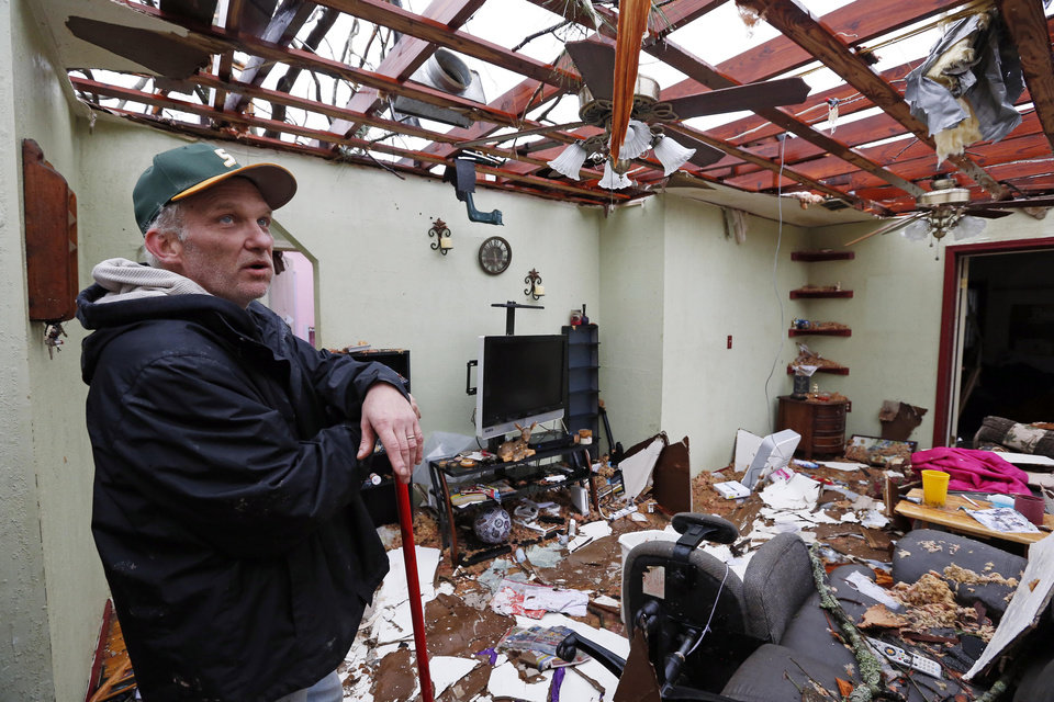 Photo - Brian Bernard looks around what remains of his living room at his Petal, Miss., home Tuesday, Feb. 12, 2013 following the  Sunday afternoon tornado. Bernard, his wife and 13-year-old daughter were hiding in a hallway when the tornado hit the house. (AP Photo/Rogelio V. Solis)