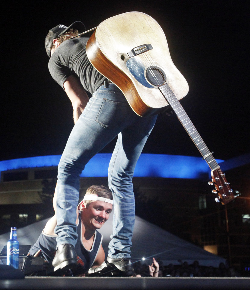 Photo - Country artist Dierks Bentley pulls a local fan onto the stage to drink a beer together after his third song of his headlining set at OKC Fest in downtown Oklahoma City on Friday, June 27, 2014. OKC Fest is a new two day country music festival with multiple stages downtown. Photos by KT King/The Oklahoman