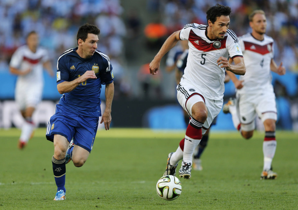 Photo - Argentina's Lionel Messi, left, and Germany's Mats Hummels go downfield during the World Cup final soccer match between Germany and Argentina at the Maracana Stadium in Rio de Janeiro, Brazil, Sunday, July 13, 2014. (AP Photo/Frank Augstein)