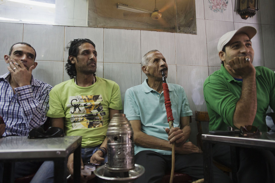 Photo - People gather in a tea shop to watch a state television broadcast as President Abdel-Fattah el-Sissi takes the oath of office, in the Zamalek district of Cairo, Egypt, Egypt, Sunday, June 8, 2014. El-Sissi was sworn in on Sunday as president for a four-year term, taking the reins of power in a nation roiled since 2011 by deadly unrest and economic woes. (AP Photo/Hiro Komae)