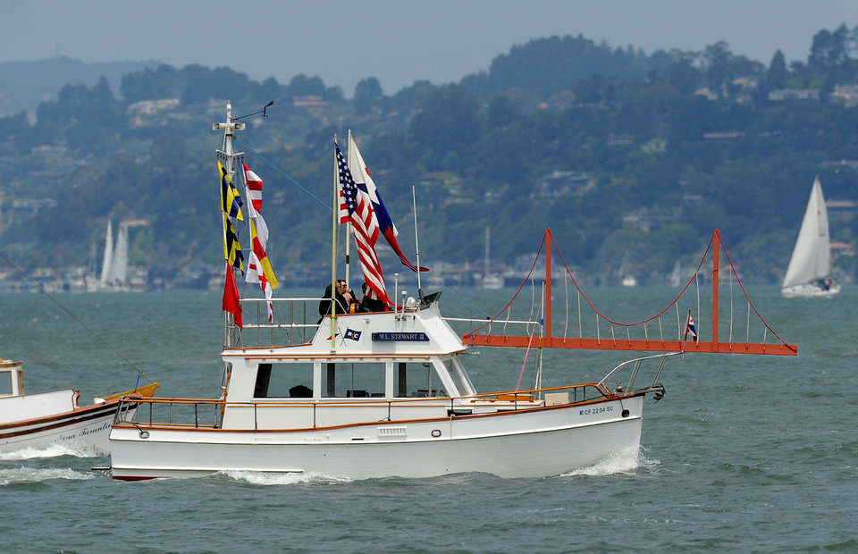 Photo -   With a sculpture of the Golden Gate Bridge adorning her foredeck, the W.L. Stewart III rides in a boat parade celebrating the Golden Gate Bridge's 75th anniversary on Sunday, May 27, 2012, in San Francisco. The commemoration included a vintage car show, an exhibit of roughly 1,558 pairs of shoes representing people who have committed suicide by jumping from the span, and a fireworks display slated for evening. (AP Photo/Noah Berger)