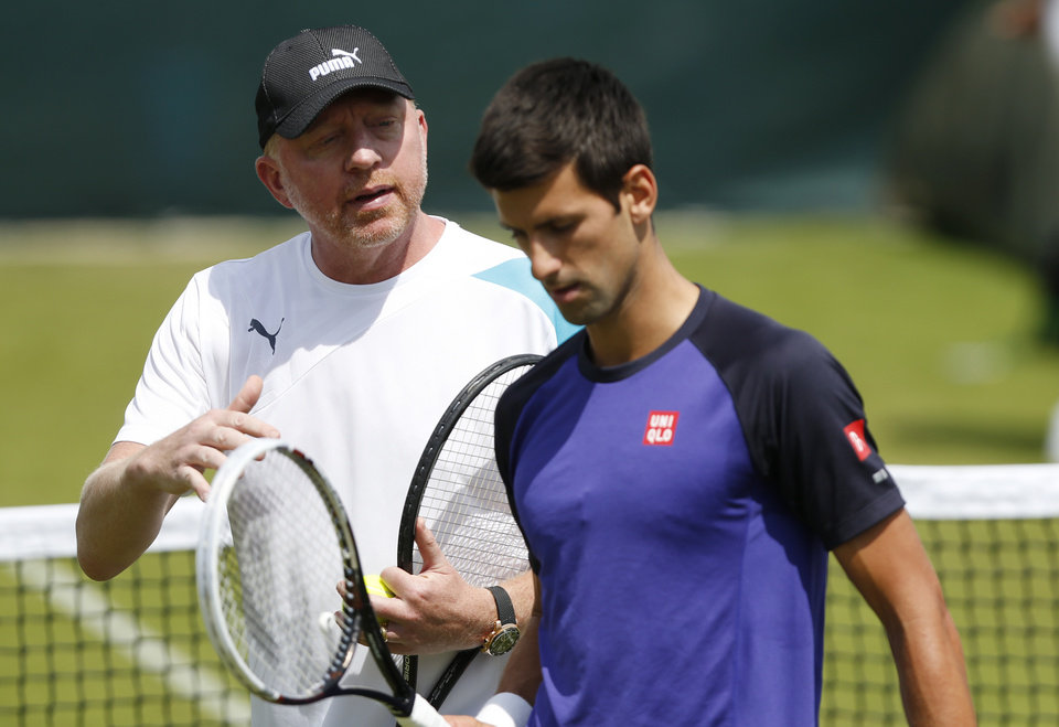 Photo - Novak Djokovic of Serbia listens to his coach Boris Becker during a practice session ahead of the All England Lawn Tennis Championships in Wimbledon, London,  Sunday June 22, 2014. (AP Photo/Sang Tan)