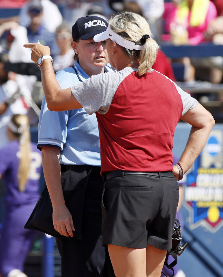 Photo -  OU coach Patty Gasso questions umpire Naomi Erdahl about a call that Washington right fielder Trysten Melhart made a catch on a Shay Knighten line drive to end the sixth inning during the second game of the Women's College World Series. [Photo by Nate Billings, The Oklahoman]