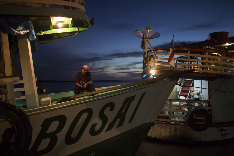 """Photo - In this May 22, 2014, photo,  a man sits on the  """"Almirante Barbosa"""" during a quick stop at the port of Manacapuru, near Manaus, Brazil. Boats like the Almirante Barbosa are the lifeline of Brazil's Amazon region, where they transport passengers and staples ranging from rice to diapers, and deliver them to remote riverside villages inaccessible any other way. (AP Photo/Felipe Dana)"""