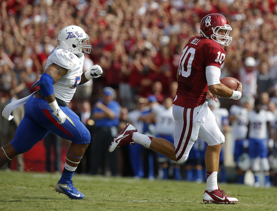 Photo - Oklahoma's Blake Bell (10) runs past Tulsa's Shawn Jackson (55) during a college football game between the University of Oklahoma Sooners (OU) and the Tulsa Golden Hurricane at Gaylord Family-Oklahoma Memorial Stadium in Norman, Okla., on Saturday, Sept. 14, 2013. Oklahoma won 51-20. Photo by Bryan Terry, The Oklahoman