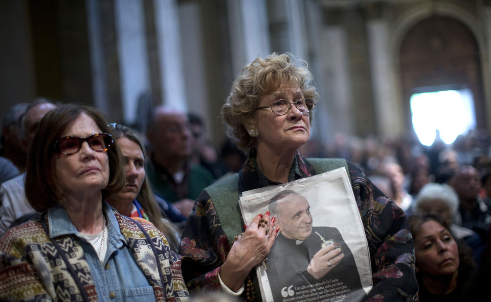 Photo - A worshiper holds a newspaper showing Pope Francis drinking mate during a Mass for the pope at the Metropolitan Cathedral in Buenos Aires, Argentina, Sunday, March 17, 2013.  Argentine's former Cardinal Jorge Mario Bergoglio was chosen as leader of the Catholic Church on March 13, 2013. (AP Photo/Natacha Pisarenko)