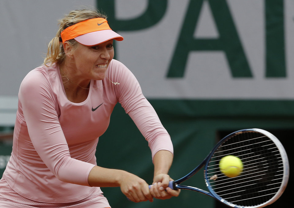Photo - Russia's Maria Sharapova returns the ball to compatriot Ksenia Pervak during their first round match of  the French Open tennis tournament at the Roland Garros stadium, in Paris, France, Monday, May 26, 2014. Sharapova won 6-1, 6-2.  (AP Photo/Michel Euler)