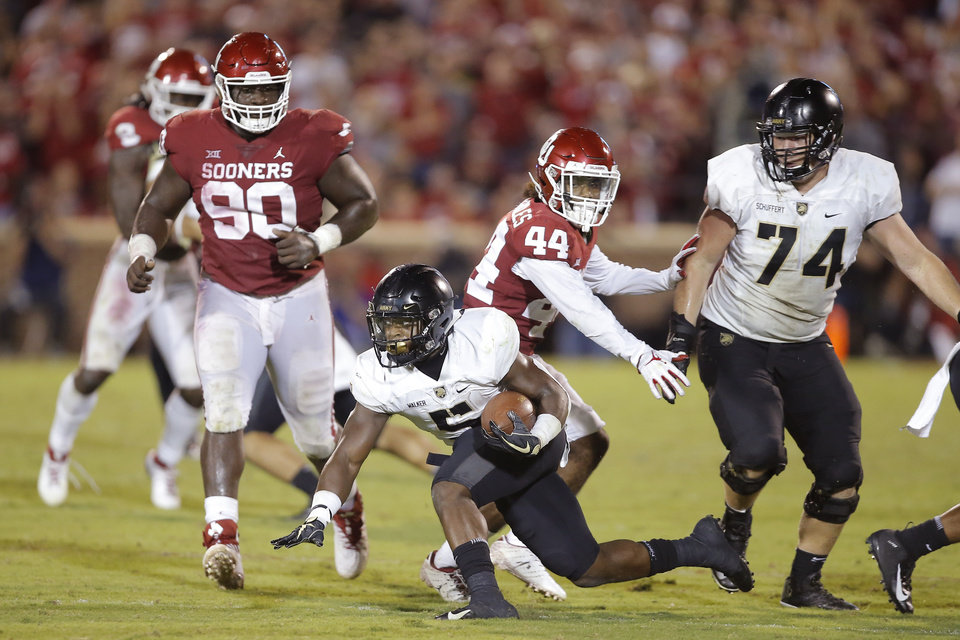Photo - Army's Kell Walker (5) keeps his balance as he carries the ball during a college football game between the University of Oklahoma Sooners (OU) and the Army Black Knights at Gaylord Family-Oklahoma Memorial Stadium in Norman, Okla., Saturday, Sept. 22, 2018. Photo by Bryan Terry, The Oklahoman