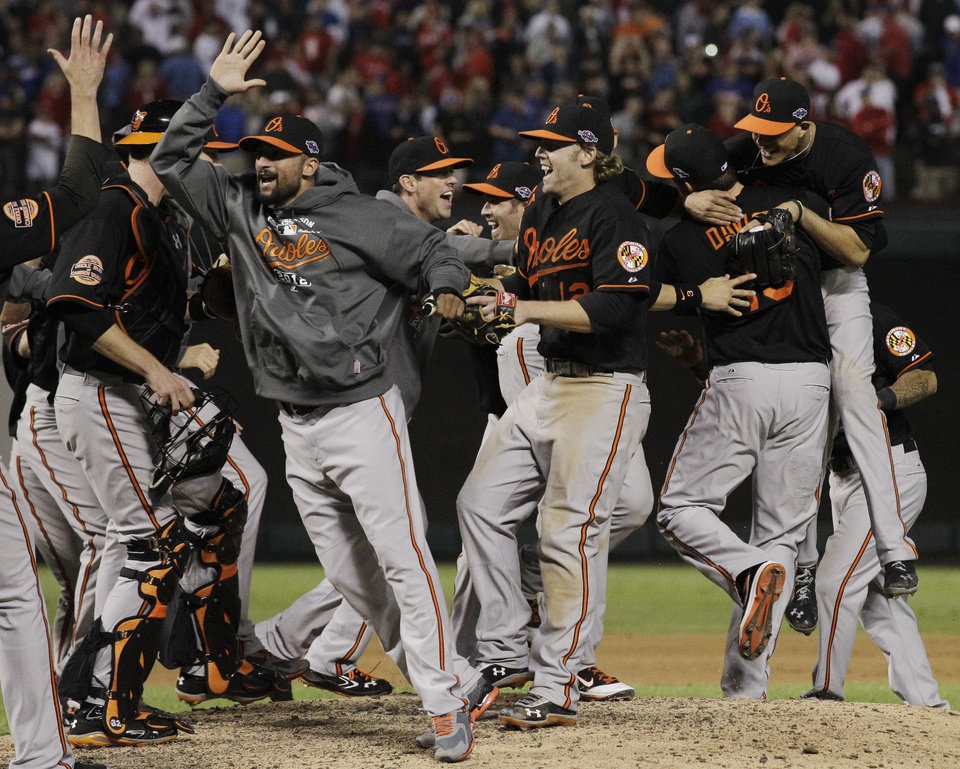 Photo -   The Baltimore Orioles celebrate winning the American League wild-card playoff baseball game against the Texas Rangers, 5-1, Friday, Oct. 5, 2012 in Arlington, Texas. (AP Photo/Tony Gutierrez)
